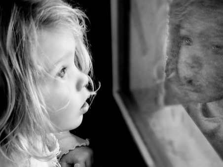 Little_girl_looking_through_window