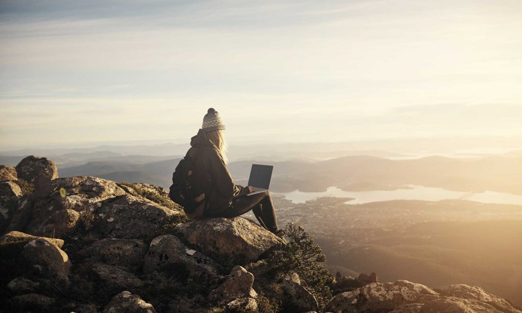girl-sitting-on-top-of-a-mountain-with-a-laptop-1024x613.jpg